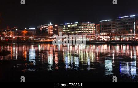 Geneva, Switzerland - November 24, 2016: Coastal cityscape with illuminated facades in central area of Geneva city at night - Stock Photo