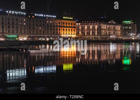 Geneva, Switzerland - November 24, 2016: Night riverside cityscape with illuminated facades in central area of Geneva city - Stock Photo