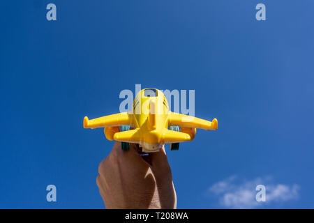 Yellow toy plane flying in to the beautiful blue sky, negative space, concept of going on a magical holiday, dream destination - Stock Photo