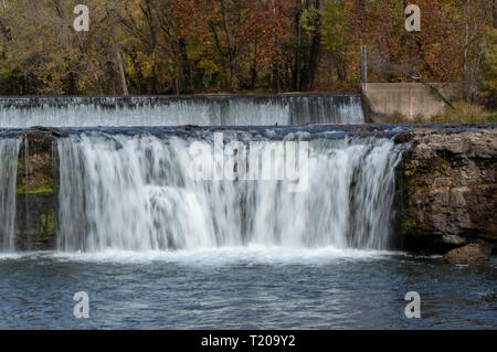 Water flows gracefully over the dam then over the rock ledge splashing into the pool below. - Stock Photo