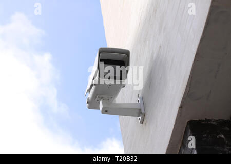 CCTV survaillance camera mounted on white building with blue sky in background - Stock Photo