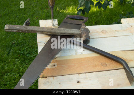 building tools hammer, axe, hacksaw frame, lie on the light boards in the garden. - Stock Photo