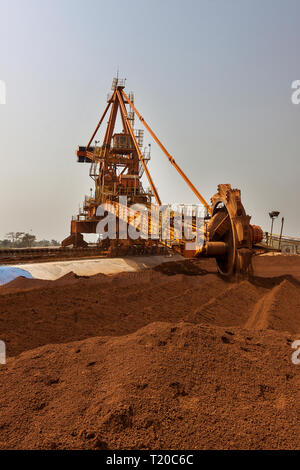 Port operations for managing and transporting iron ore.  Bucket  reclaimmer stacker using bucket wheel to move lump ore to conveyor before shipping. - Stock Photo