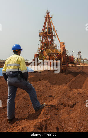 Port operations for managing and transporting iron ore.  Bucket  reclaimmer stacker using bucket wheel to move lump ore to conveyor and supervisor - Stock Photo