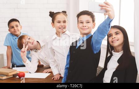 Happy children taking selfie at school classroom during break - Stock Photo