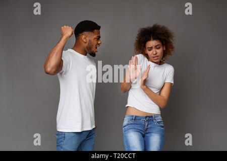Female discrimination at home. African-american man beating his wife, black studio background - Stock Photo