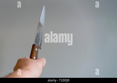 Man's hand with a knife on gray background. Concept of violence. Hand of a gangster with a knife. - Stock Photo