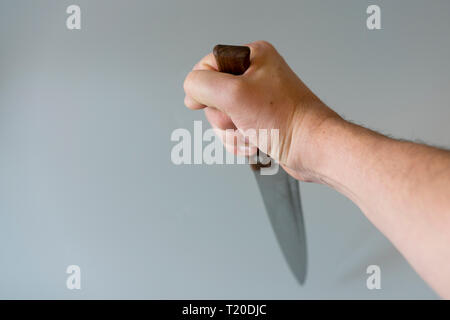Man's hand with a knife on gray background. Concept of violence. Hand of a gangster with a knife. copy space. - Stock Photo