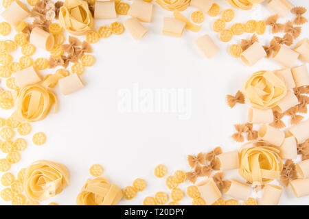 An overhead photo of different types of pasta, including spaghetti, penne, fusilli, and others, flay lay on a white background with a place for text - Stock Photo