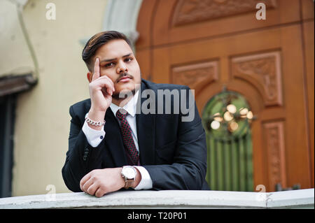 Stylish indian businessman in formal wear leaning on a railing against door in business center. Finger at the temple as thinking man. - Stock Photo