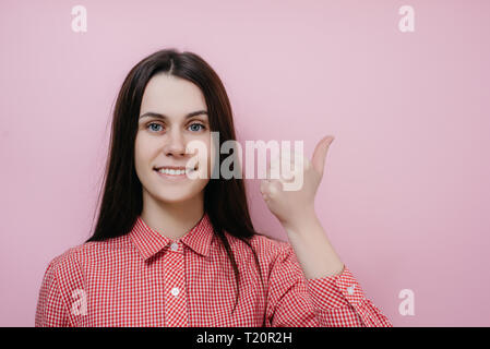 Amused pleasant looking positive young woman points on right, dressed in casual shirt, shows free space against pink background, suggests going there, - Stock Photo