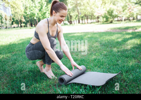 Girl in grey sport costume is almost sitting and rolling up the carimate. She is doing that very accurate and careful. Yoga and Pilates Concept - Stock Photo