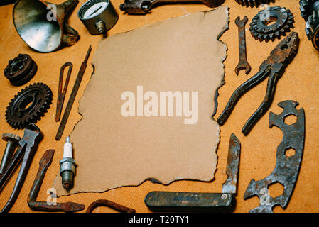 Vintage paper for your info in the center of rusty tools, gears on vintage fiberboard background. Motorcycle equipment and repair template. - Stock Photo