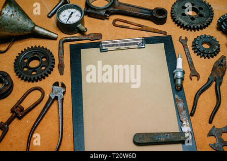 Clipboard with paper for your info in the center of rusty tools, gears on vintage fiberboard background. Motorcycle equipment and repair template. - Stock Photo