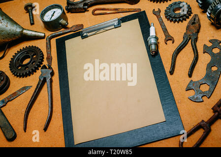 Closeup clipboard with paper for your info in the center of rusty tools, gears on vintage fiberboard background. Motorcycle equipment and repair templ - Stock Photo