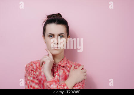 Horizontal portrait of lovely female student with hair knot, holds chin, wears shirt, looks seriously and with shy expression at camera, isolated on p - Stock Photo
