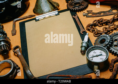Closeup clipboard with paper for your info in the center of rusty tools, gears on vintage metal background. Motorcycle equipment and repair template. - Stock Photo