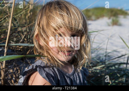 Denmark, Bornholm, portrait of smiling girl on Dueodde white sand beach - Stock Photo