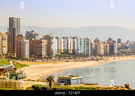 Downtown buildings and towers with road, sandy beach and sea in the foreground, Beirut, Lebanon - Stock Photo