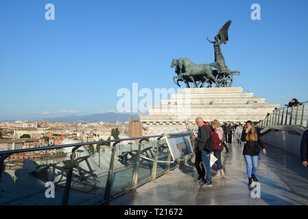 Tourists Enjoy Panoramic Views over the Rooftops of Rome from the Vittorio Emanuele II Monument with Winged Victory Sculpture Rome Italy - Stock Photo