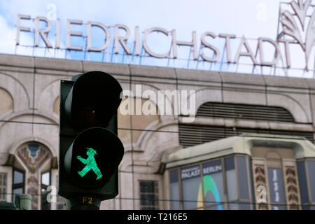 Green traffic light man in front of the lettering of the Friedrichstadt Palace in Berlin Mitte. - Stock Photo
