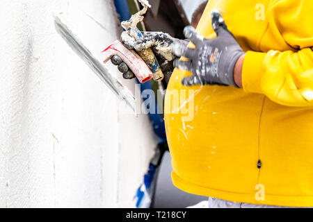 MOERS / GERMANY - MARCH 26 2019 : Construction worker plastering and smoothing concrete wall with cement. - Stock Photo