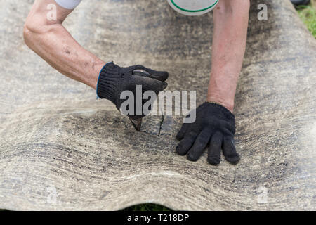Man's hands cutting roofing material. Ruberoid. Worker