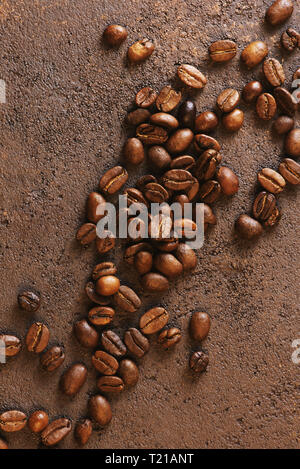 Coffee beans on the textured brown table, top view composition - Stock Photo