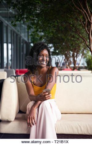 An Afro-Brazilian woman sitting in a garden lounge in Rio de Janeiro, Brazil - Stock Photo