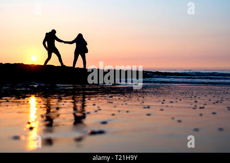 Norderney, Germany. 29th Mar, 2019. A couple walks before the setting sun over a stage on the west beach of the island. Spring weather in the interior and on the coast, temperatures around 20 degrees Celsius lure people outside. Credit: Hauke-Christian Dittrich/dpa/Alamy Live News - Stock Photo