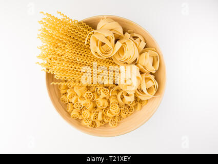 Pasta in bowl, isolated on white background, top view - Stock Photo