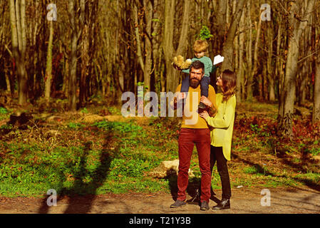People relax in spring park outdoor. Mother and father piggybacking cute small son, people concept. Fun and play all day - Stock Photo
