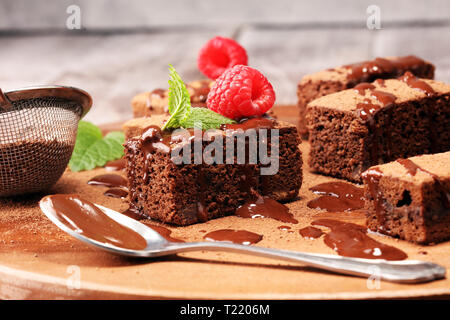 chocolate brownie cake dessert with raspberries and spices on a wooden background. - Stock Photo