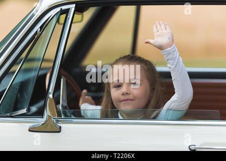 Little girl driving a car - Stock Photo