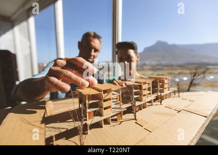 Architects discussing over architectural model - Stock Photo