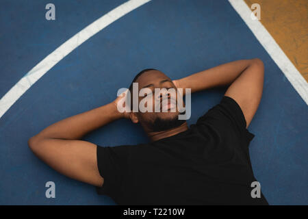 Basketball player relaxing on the floor in basketball court - Stock Photo