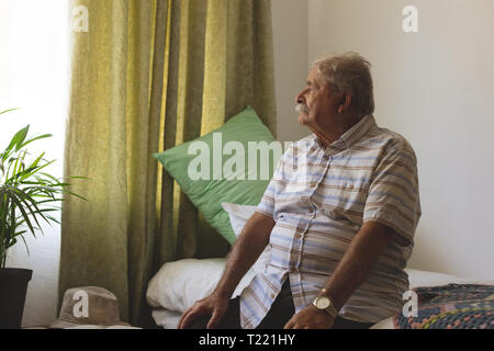 Senior man looking outside the window while sitting alone at nursing home - Stock Photo