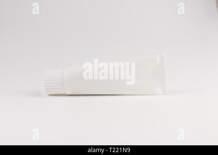 Blank white tube of toothpaste, cream or gel laying on white background, isolated on white - Stock Photo