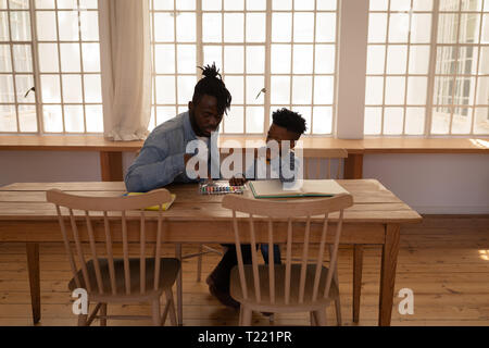 Father assisting his son in drawing while sitting on chair at dining room - Stock Photo