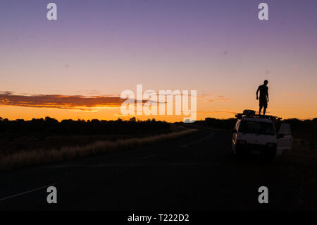 young man standing on car while a nice Sunset in the Outback of Australia - Stock Photo