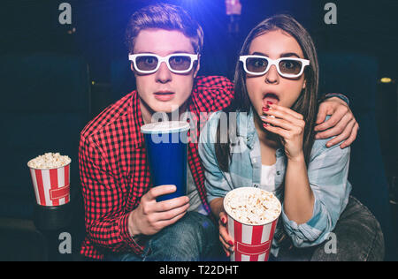 Portrait of two people sitting together in cinema hall and wearing glasses. Girl is amazed and eating popcorn while her partner is drinking cola - Stock Photo