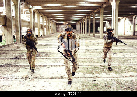 Three warriors with equipment is running down big and bright room. Two of them are looking to the sides while the man in front is looking straight and - Stock Photo