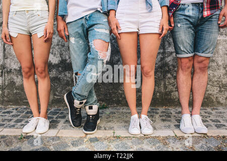 A picture of teens' legs. Three of them are standing straight while man in jeans is holding left leg over right one. Girls wear shorts and one boy as  - Stock Photo