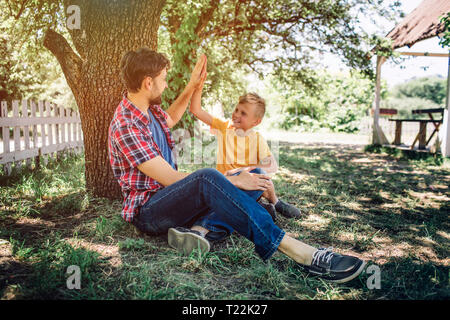Boy and adult guy are sitting and playing with each other. Child is giving high-five to his dad. They are smiling to each other. Boys are happy - Stock Photo