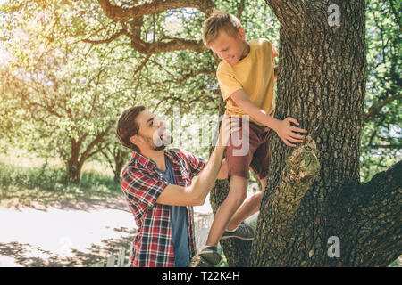 Father and son are playing with each other. Guy is supporting his child. Boy is looking down at father. They are smiling. Both of them are happy - Stock Photo