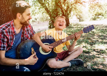 Joyful and satisfied young boy is holding guitar and playing on it. He is singing and keeping eyes closed. His father is helping him. He is proud of s - Stock Photo
