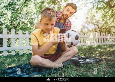 Bearded man is sitting on the back from his son, He wants to play footbll game with child. Kid is not interested in that. He is playing with phone - Stock Photo