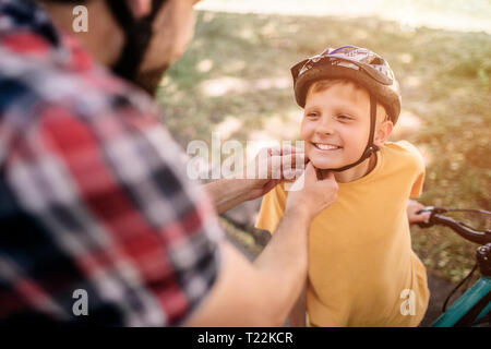 Adult man is locking the helmet of his son. He is doing that very accurate. Boy is standing besides his dad and smiling - Stock Photo