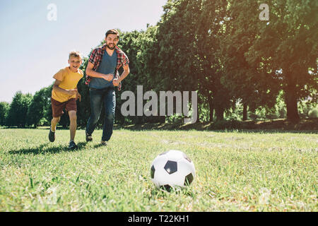 Father and son are playing football. They are running together. Boys want to reach the ball first - Stock Photo