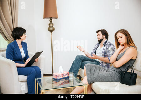 Beautiful young couple is sitting on sofa. Man is talking to psychologist. Doctor is listening to him. Girl is upset - Stock Photo